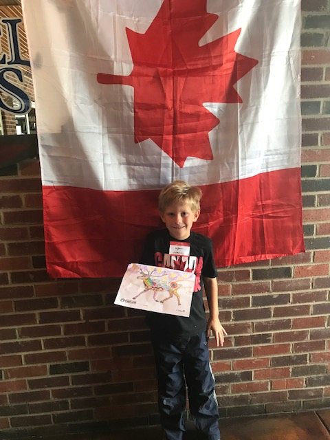 Young winner of drawing contest posing with his drawing in front of Canada flag
