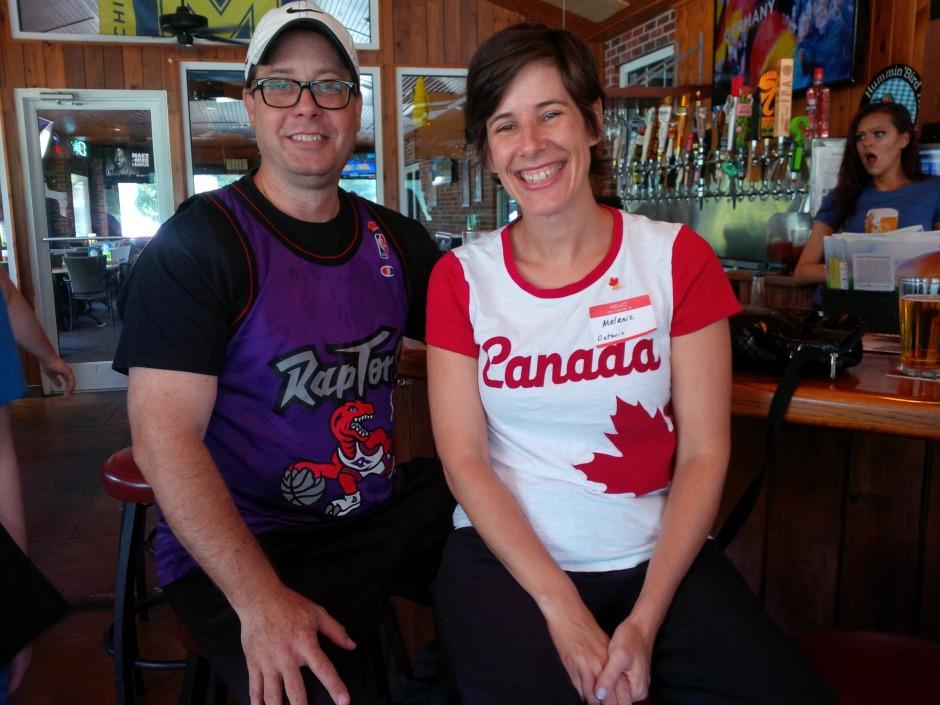 Man wearing Toronto Raptors shirt and woman wearing Canada shirt