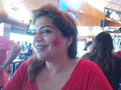 Woman with a painted maple leaf on her cheek