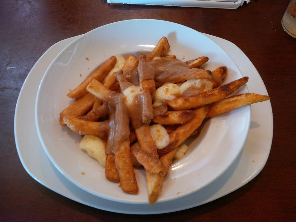 Plate of poutine: fries, gravy and cheese curds